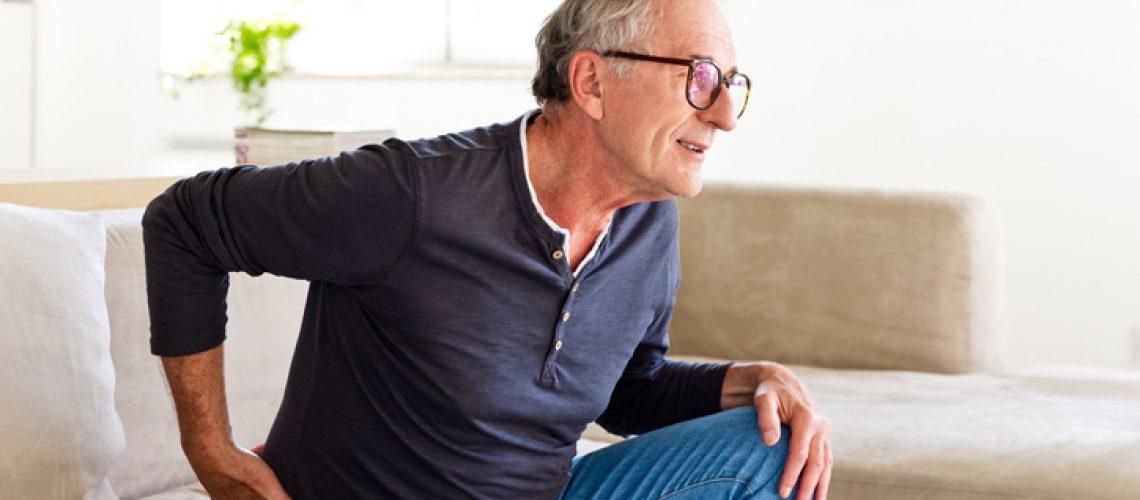 Worried senior man sitting on sofa at home and touching his back. Elderly man suffering lumbar spine.