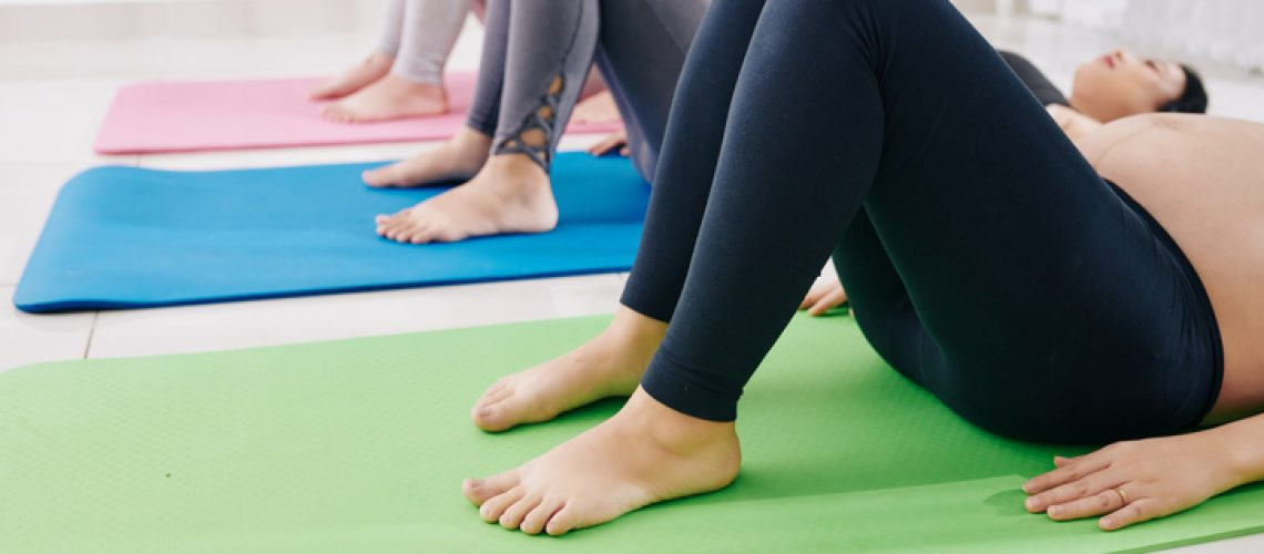 Group of young pregnant women lying on yoga mats when tonning up muscles of pelvic floor